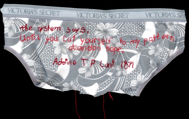 A grey and white floral pair of underwear is embroidered with the quote using wine and salmon colored thread