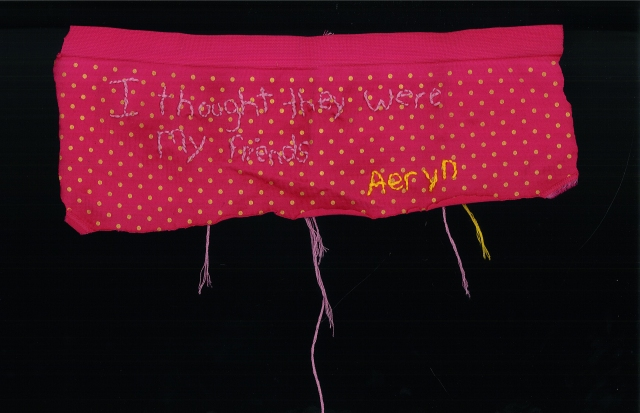 The quote is embroidered using light purple thread and the name is in yellow. Both are embroidered onto a pair of pink and yellow boyshort underwear