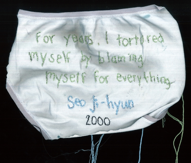 a small pair of white underwear is embroidered with a quote from Seo Ji-hyun using a soft green and blue thread
